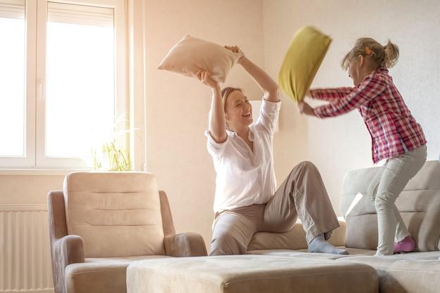 Mujer caucásica jugando con almohadas con su hija de 6 años en el sofá de su casa