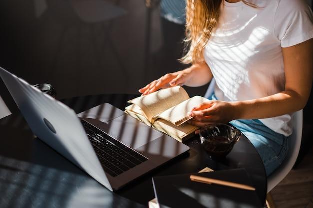 Mujer caucásica libro de lectura en la parte delantera del portátil en la cocina en la mañana soleada y tomando café
