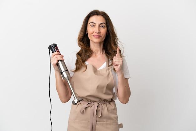 Mujer caucásica de mediana edad con batidora de mano aislado sobre fondo blanco pensando en una idea apuntando con el dedo hacia arriba