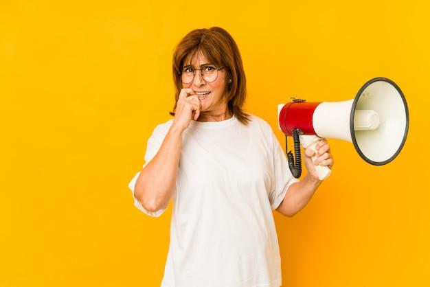 Mujer caucásica de mediana edad sosteniendo un megáfono relajado pensando en algo mirando un espacio de copia.
