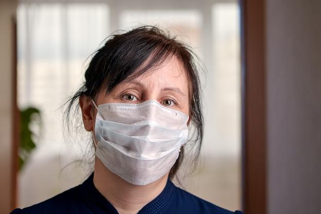 Mujer caucásica de mediana edad usa mascarilla quirúrgica o mascarilla de un solo uso.