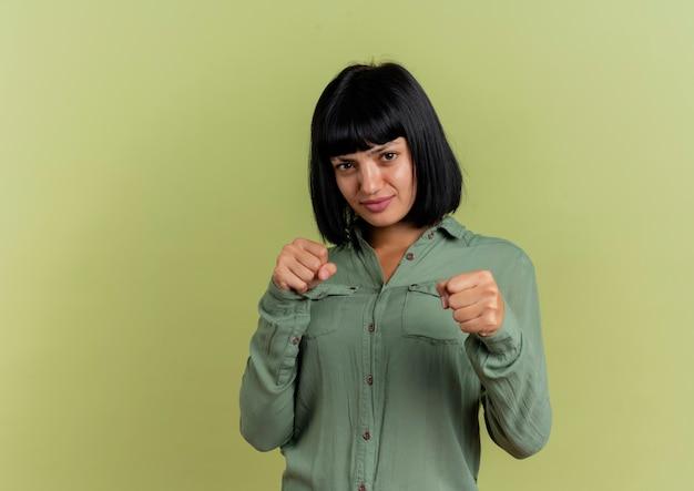 Mujer caucásica morena joven disgustada mantiene los puños listos para perforar aislado sobre fondo verde oliva con espacio de copia