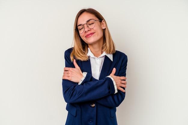 Mujer caucásica de negocios joven abrazos, sonriendo despreocupado y feliz.