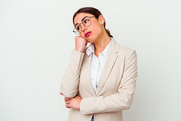 Mujer caucásica de negocios joven aislada sobre fondo blanco que se siente triste y pensativa, mirando el espacio de la copia.