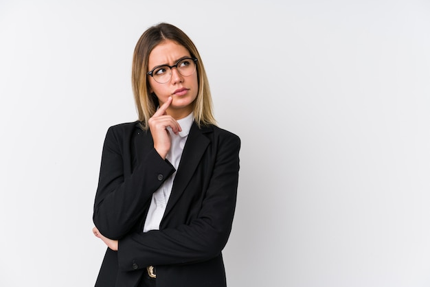 Mujer caucásica de negocios joven mirando hacia los lados con expresión dudosa y escéptica.