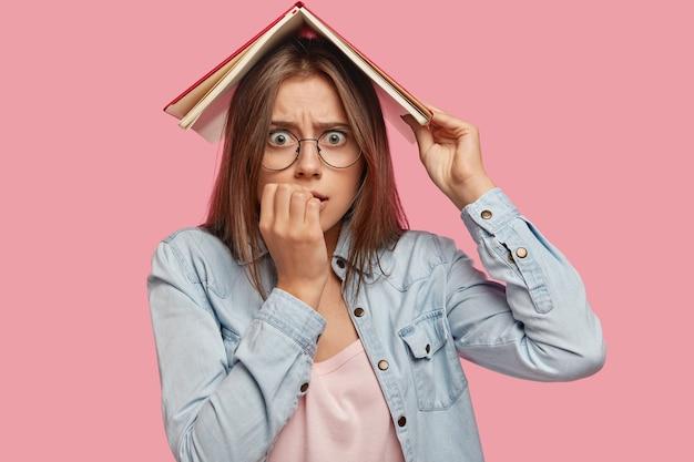 Mujer caucásica nerviosa ansiosa se muerde las uñas, sostiene el libro sobre la cabeza, se preocupa antes de aprobar el examen, posa contra el fondo de color rosa. el estudiante mira nerviosamente. concepto de educación y personas