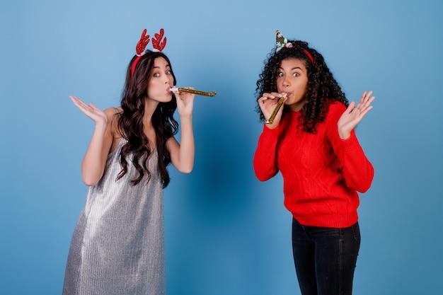 Mujer caucásica y niña negra soplando silbatos de navidad aislado sobre azul