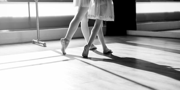 Una mujer caucásica y una niña practicando ballet