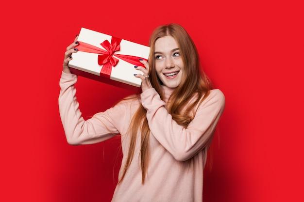 Mujer caucásica con pecas y cabello rojo está agitando un presente posando en la pared roja del estudio