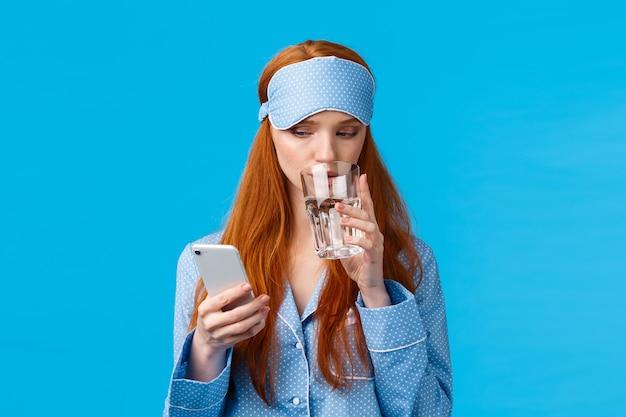 Mujer caucásica pelirroja concentrada y adicta al teléfono con antifaz para dormir glamour