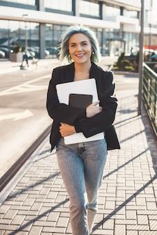 Mujer caucásica de pelo azul con portátil caminando a una reunión de negocios mirando al frente