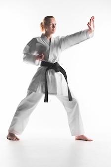 Mujer caucásica practicando karate tiro completo