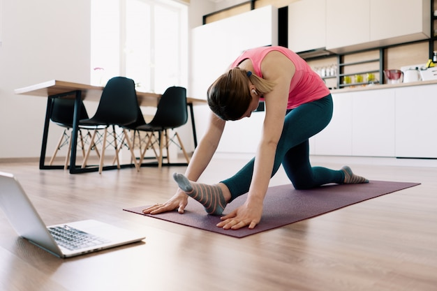 Mujer caucásica practicando yoga en casa
