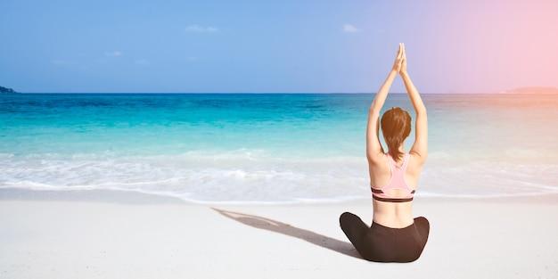 Mujer caucásica practicando yoga en la orilla del mar
