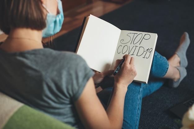 Mujer caucásica preocupada con máscara blanca está sentada en el sofá y escribe stop covid-2019 en un libro