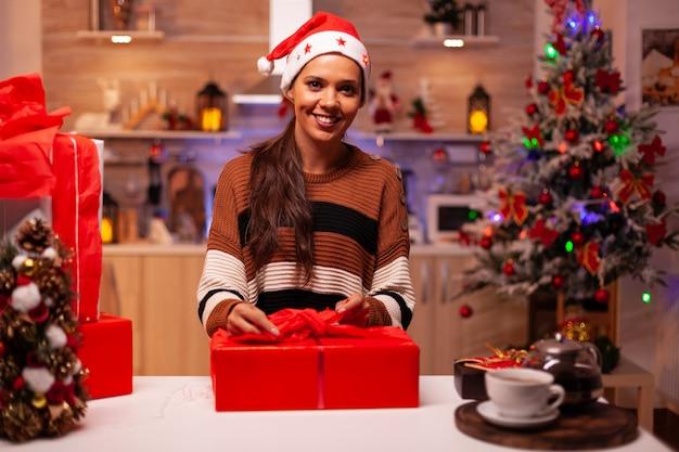 Mujer caucásica preparando cajas de regalo con cinta