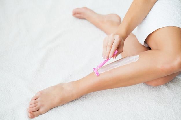 Mujer caucásica que afeita las piernas con la maquinilla de afeitar en casa