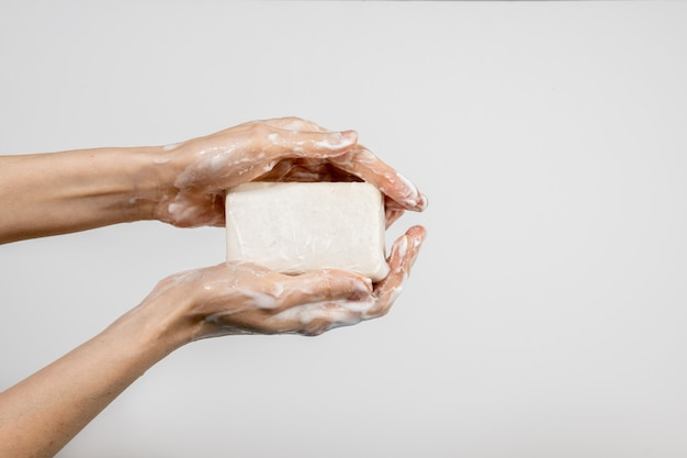 Mujer caucásica que se lava las manos con una pastilla de jabón burbujeante aislada en la pared blanca