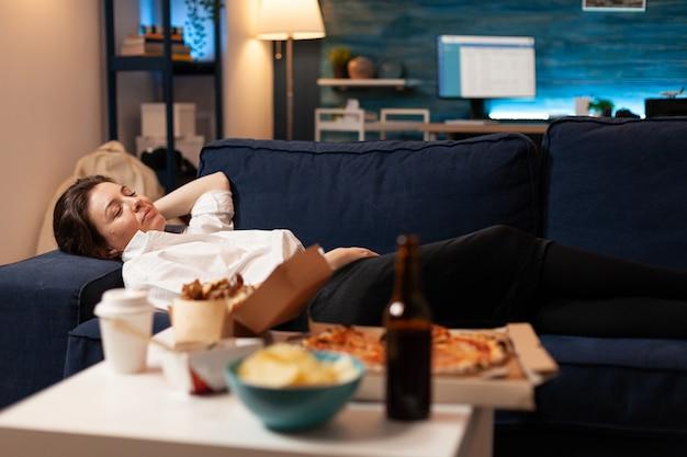 Mujer caucásica quedarse dormido después de comer comida chatarra en el salón a altas horas de la noche