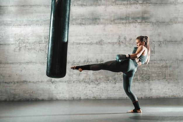 Mujer caucásica en ropa deportiva y con guantes de boxeo pateando el bolso en el gimnasio.