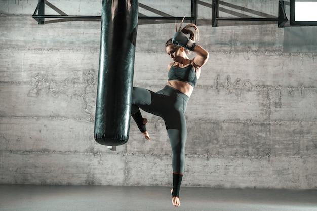 Mujer caucásica en ropa deportiva y con guantes de boxeo pateando el saco en el gimnasio. longitud total.