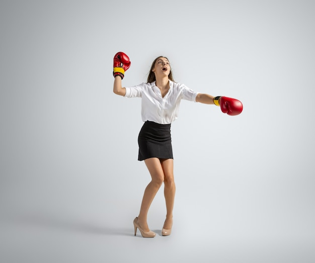 Mujer caucásica en ropa de oficina de boxeo en gris