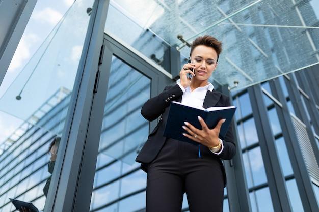 Mujer caucásica en ropa de oficina escribe en el cuaderno y espera colega cerca del edificio de oficinas
