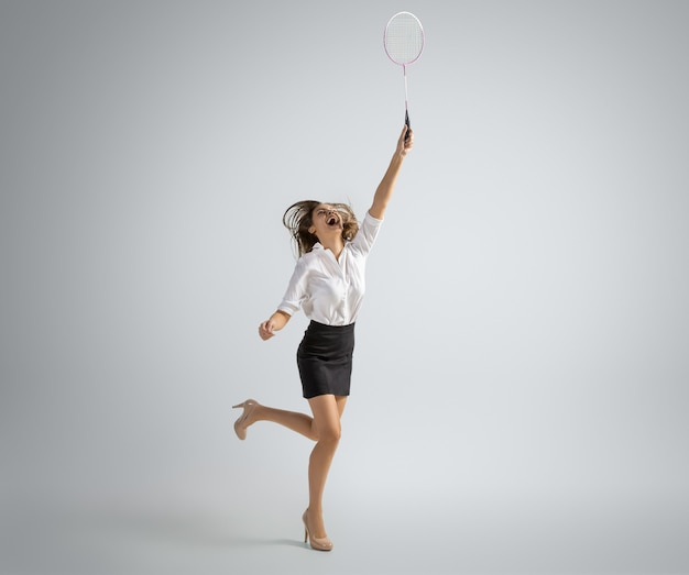 Mujer caucásica en ropa de oficina juega bádminton aislado en la pared gris