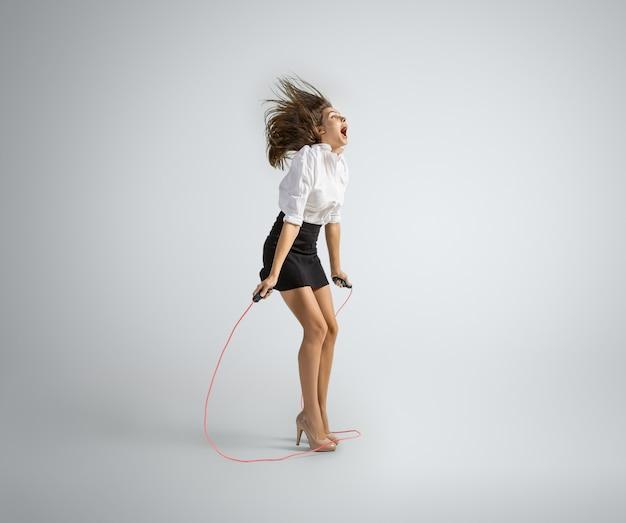 Mujer caucásica en ropa de oficina saltando con cuerda en gris