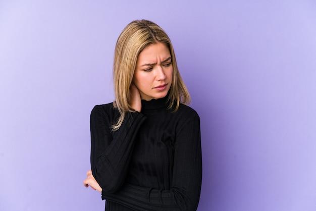 Mujer caucásica rubia joven aislada que tiene un dolor de cuello debido al estrés, masajeando y tocándolo con la mano.