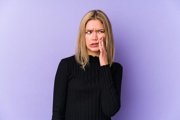 Mujer caucásica rubia joven aislada que tiene un dolor de dientes fuerte, dolor molar.