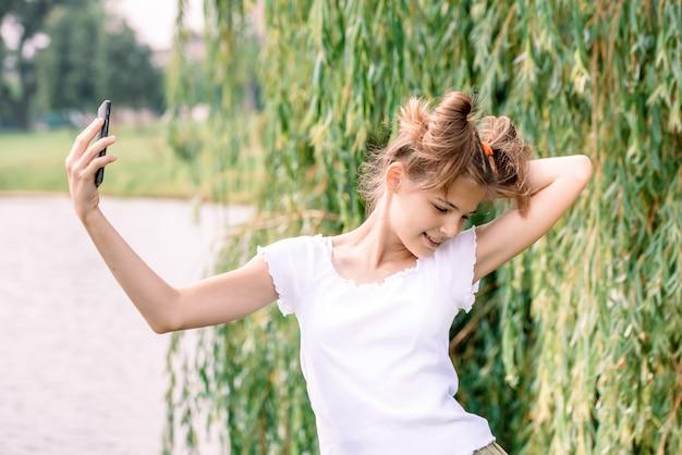 Mujer caucásica rubia joven hermosa con el café para llevar que toma un selfie con smartphone al aire libre en parque en otoño.