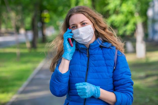 Una mujer caucásica rubia con máscara protectora y guantes está caminando por la calle vacía y hablando por teléfono. comportamiento seguro