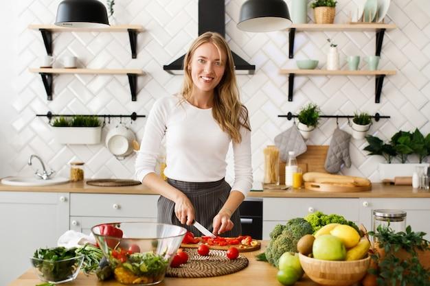 La mujer caucásica rubia sonrió está cortando el pimiento rojo en la cocina moderna en la mesa llena de frutas y verduras frescas