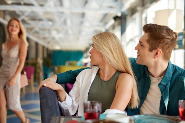 Mujer caucásica rubia vino a amigos sentados en el café