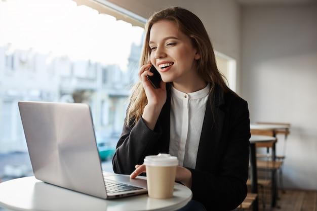 Mujer caucásica sentada en la cafetería, tomando café, hablando por teléfono inteligente, mirando la pantalla del portátil con una amplia sonrisa