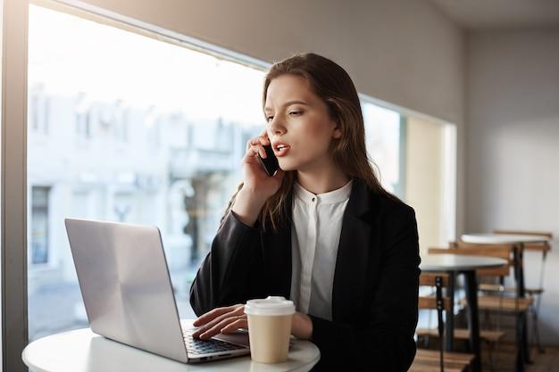 Mujer caucásica sentado en la cafetería con laptop, tomando café, hablando por teléfono inteligente