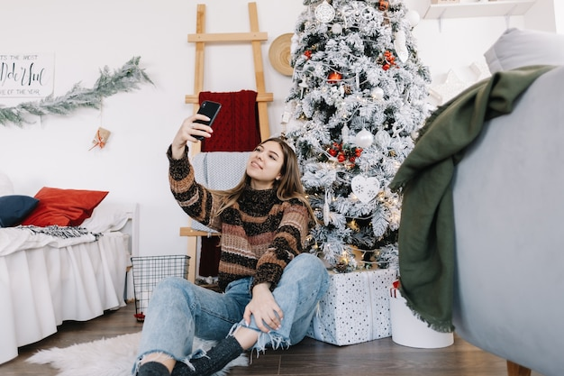 Mujer caucásica sonriente joven que hace selfie usando el teléfono móvil cerca del árbol de navidad en casa.