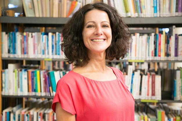 Mujer caucásica sonriente que presenta en la biblioteca pública