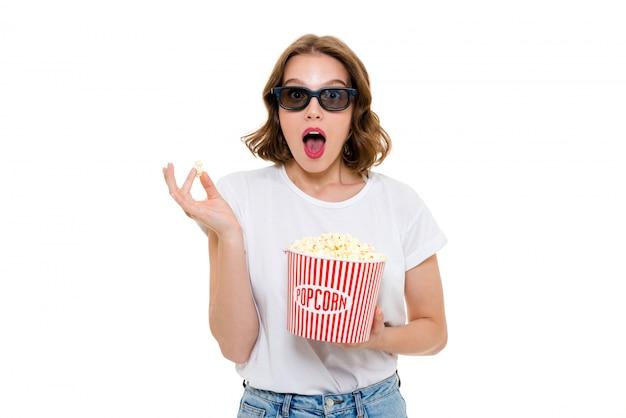 Mujer caucásica sorprendida con palomitas de maíz con gafas 3d