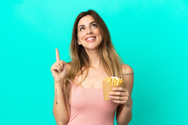 Mujer caucásica sosteniendo patatas fritas aisladas sobre fondo azul apuntando hacia una gran idea