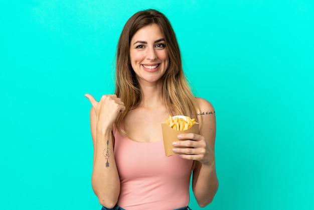 Mujer caucásica sosteniendo patatas fritas aisladas sobre fondo azul apuntando hacia el lado para presentar un producto