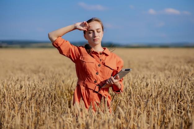 Mujer caucásica tecnólogo agrónomo con tablet pc en el campo de trigo, control de calidad