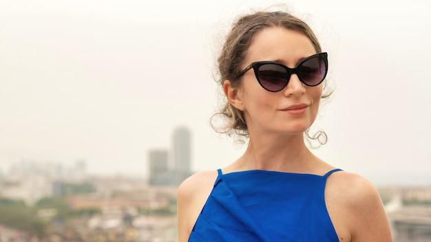 Mujer caucásica en vestido azul con vista de barcelona al fondo, españa