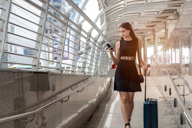 La mujer caucásica del viajero en aeropuerto lleva la maleta que espera viaje aéreo usando el teléfono inteligente.