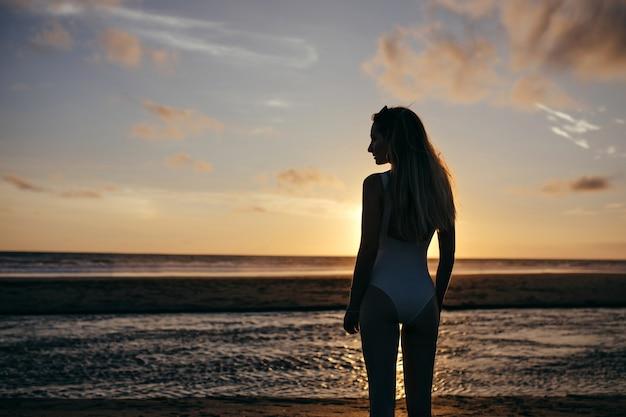 Mujer caucásica viste traje de baño blanco en vacaciones. señora joven despreocupada disfrutando de la noche en el océano y mirando la hermosa puesta de sol.