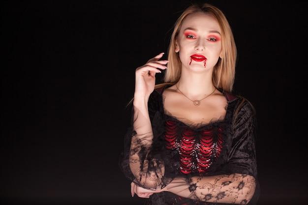Mujer caucásica vistiendo un seductor disfraz de vampiro para halloween. mujer atractiva.