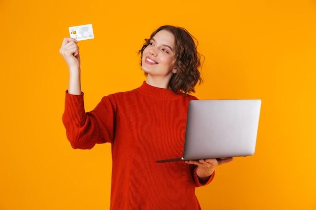 Mujer caucásica vistiendo un suéter usando una computadora portátil plateada y una tarjeta de crédito mientras se encuentra aislado en amarillo