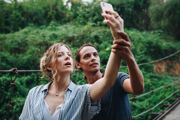 Mujer caucásica y hombre tomando un selfie al aire libre ocio recreativo