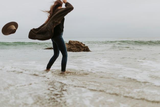 Mujer cayendo su sombrero debido al viento en la playa